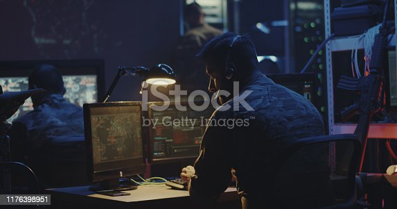 Medium shot of a soldier working on a computer