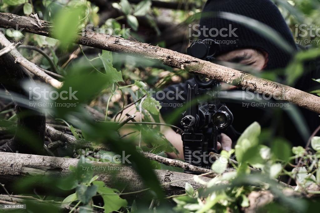 Soldiers aiming target and holding his rifles hidden ambushed, Army sniper camouflage in forest, Battle in the woods. stock photo