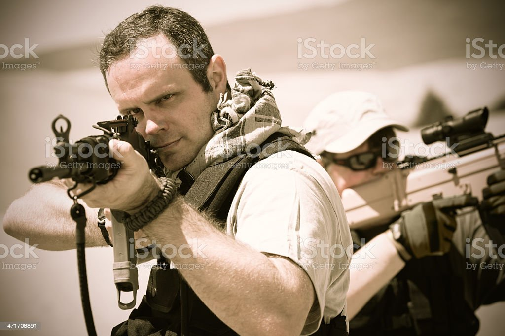 Soldiers aiming weapons during desert training exercise royalty-free stock photo