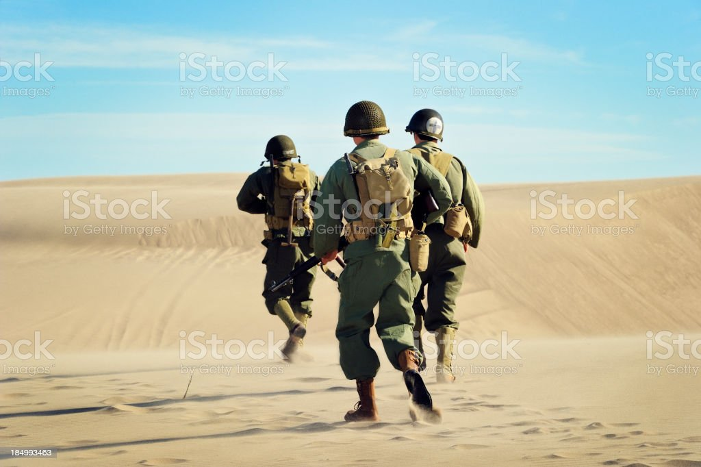 WWII Soldiers and Medic On Patrol In The Desert stock photo