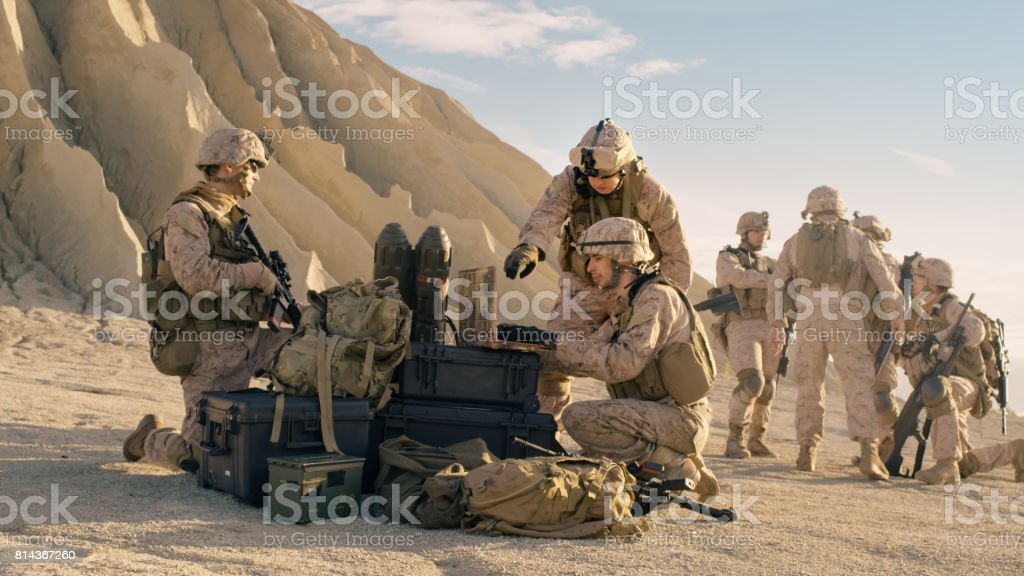 Soldiers are Using Laptop Computer for Surveillance During Military Operation in the Desert. stock photo