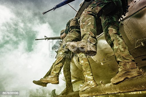 istock Soldiers boarding a military helicopter was landing in the jungle, Soldiers running through a sandstorm. 867638596