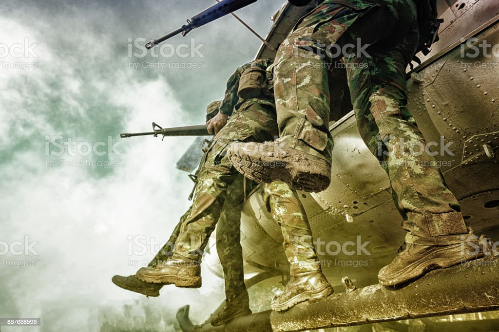 Soldiers boarding a military helicopter was landing in the jungle, Soldiers running through a sandstorm. stock photo