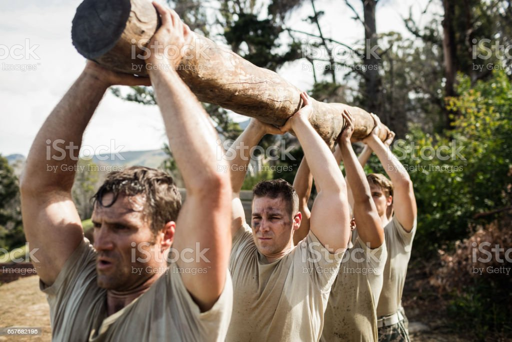 Soldiers carrying a tree log stock photo