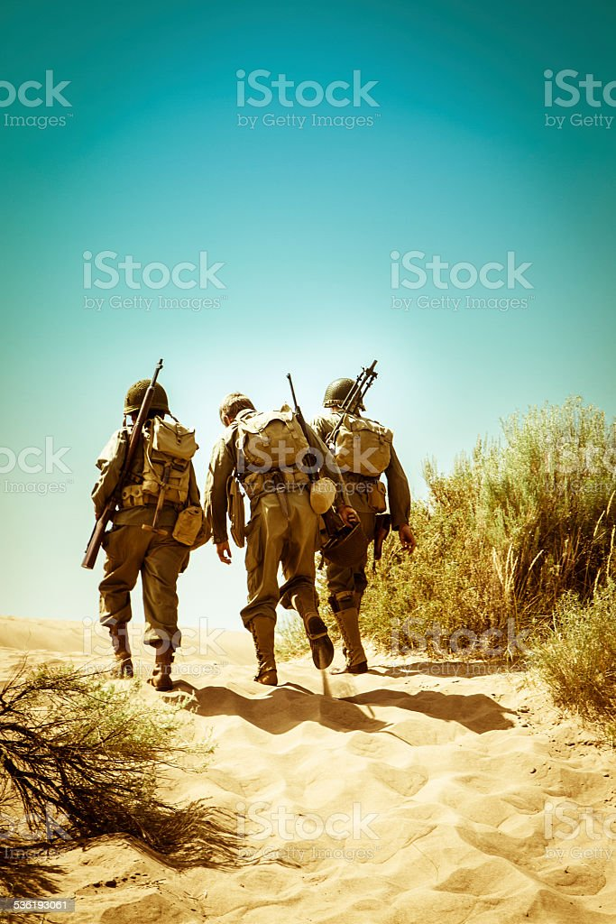 WWII Soldiers Climbing A Hill Together stock photo