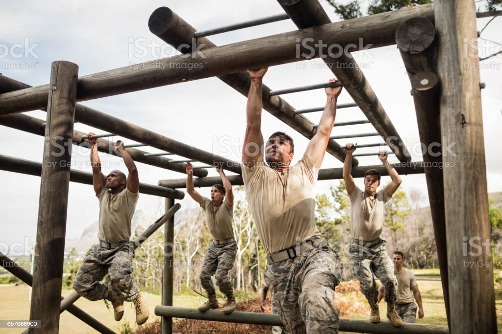 Soldiers climbing monkey bars stock photo
