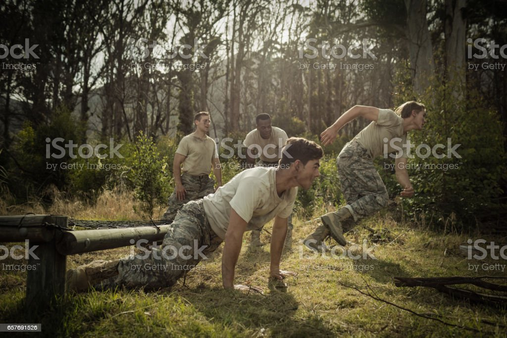 Soldiers crawling under the net during obstacle course stock photo