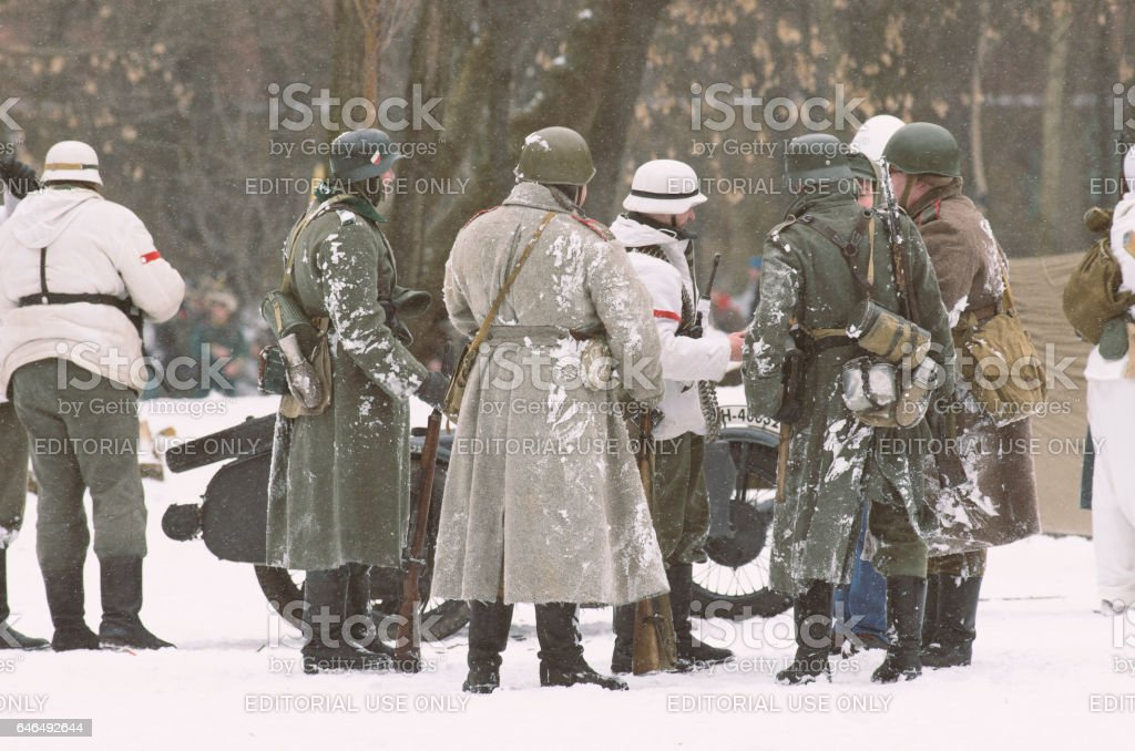 Soldiers dressed in overcoats, camouflage suits and armed with rifles. stock photo