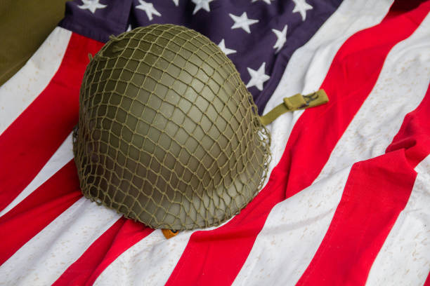 soldier's helmet and the times of the second world war and the us flag. patriotism - world war ii stock photos and pictures
