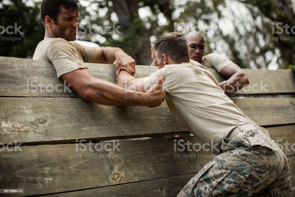 Soldiers helping man to climb wooden wall stock photo