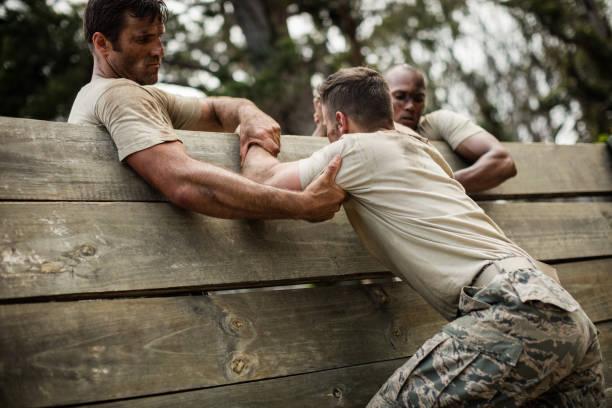 soldaten helfen holzwand erstbesteiger - militärisches training stock-fotos und bilder