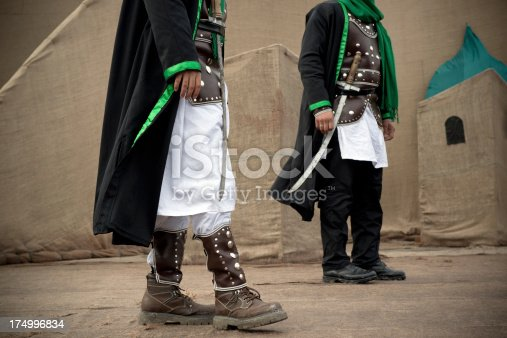 Two unrecognized soldiers wearing local cloths and holding their swords.