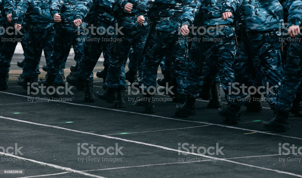 Soldiers in blue camo marching on ground stock photo