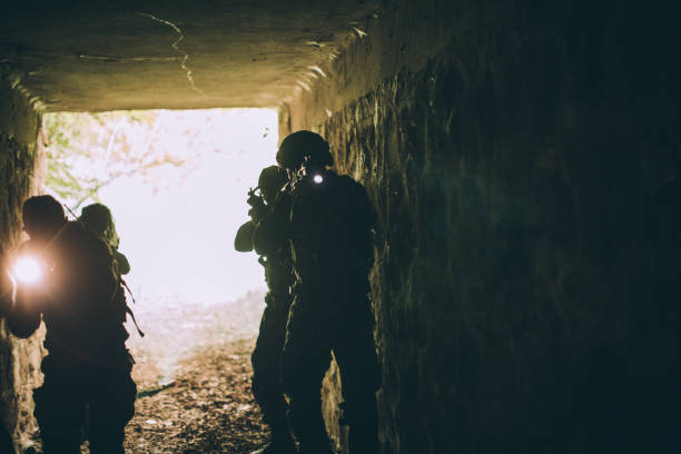 Soldiers in dark cave Group of soldiers in camouflaged clothing on a mission in dark cave. counter terrorism stock pictures, royalty-free photos & images
