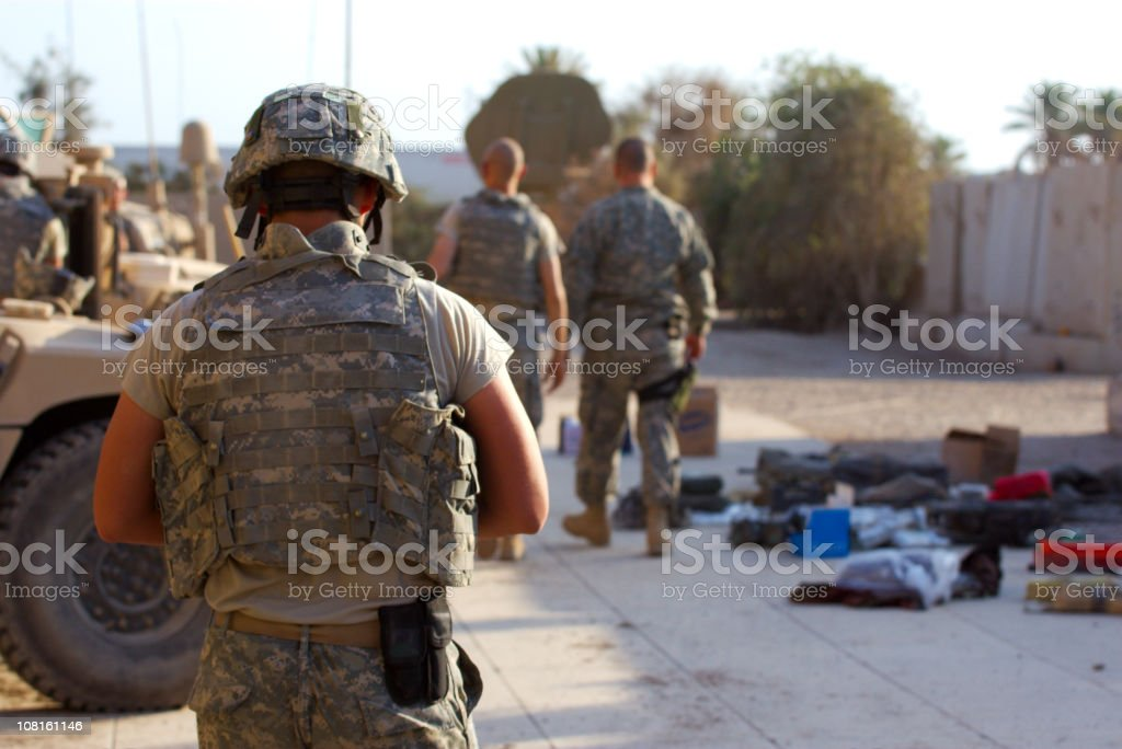 Soldiers in desert fatigues with vehicles in the background stock photo