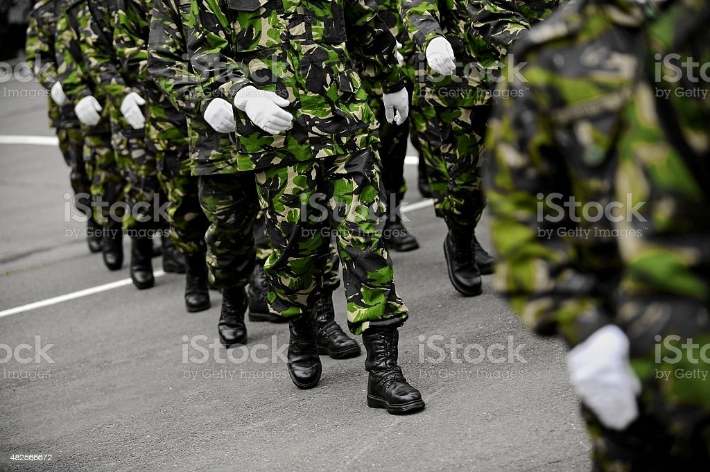Soldiers in green camouflage marching stock photo