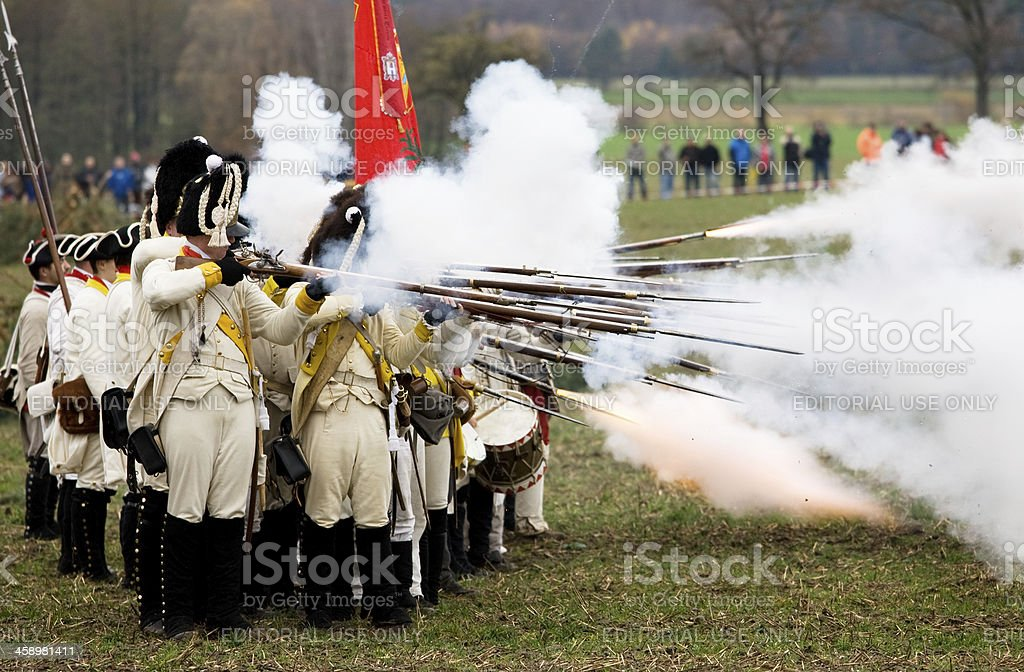 soldiers in historic regimentals firing off muskets stock photo