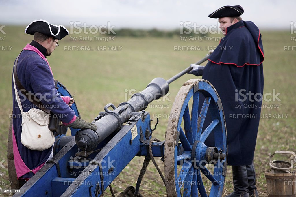 soldiers in historic regimentals reloading medieval cannon stock photo