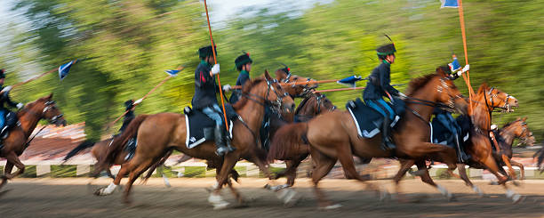 Soldiers in historical uniform on horseback simulating a cavalry charge stock photo