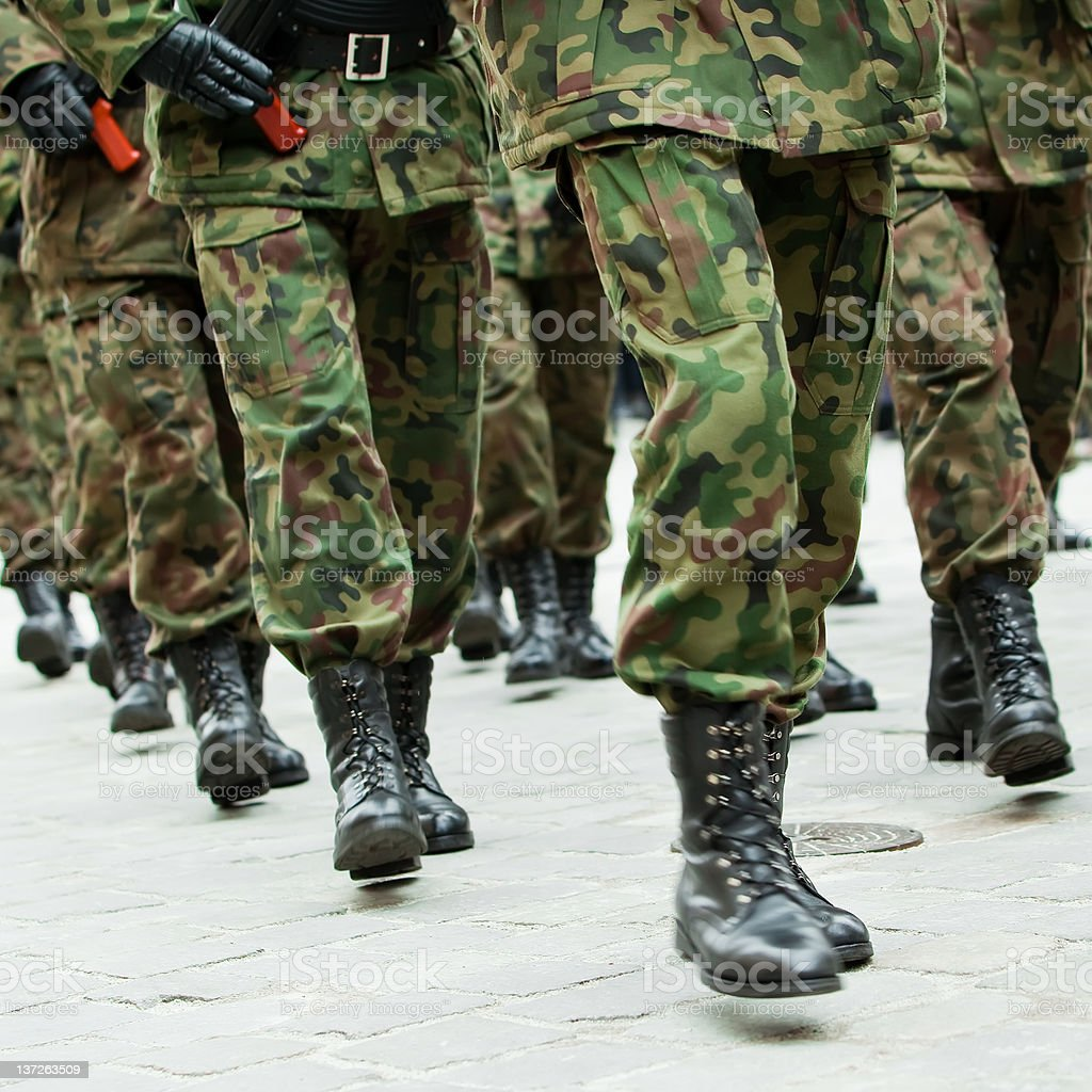 Soldiers marching in unison on cobblestone stock photo