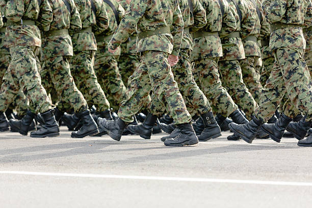 Soldiers marching Unrecognizable soldiers marching in camouflage uniforms, copy space military parade stock pictures, royalty-free photos & images