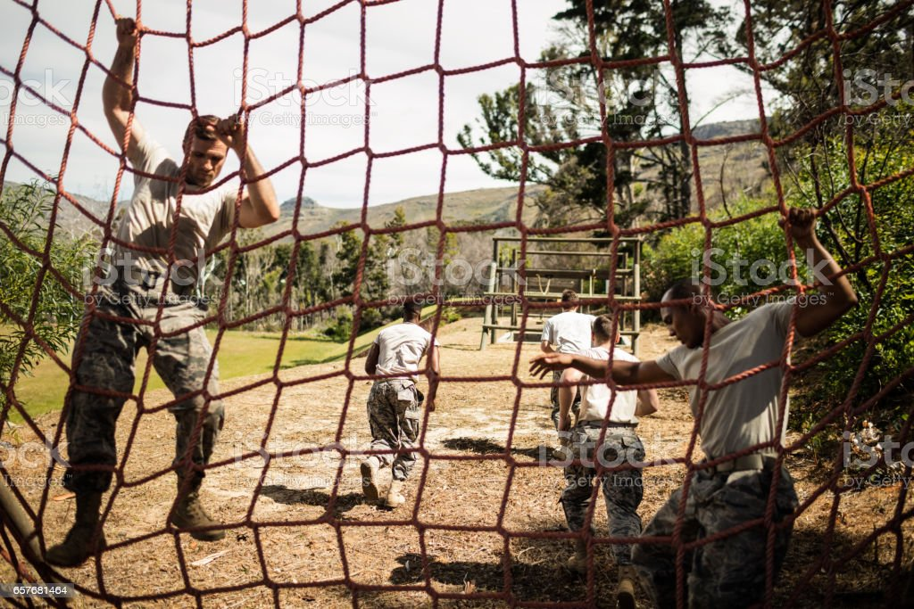 Soldiers performing training exercise on net stock photo