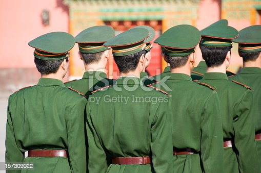 Unrecognizable group of soldiers standing in line and seen from behind. Wearing uniforms including caps. The soldiers belong to the Chinese armed forces.