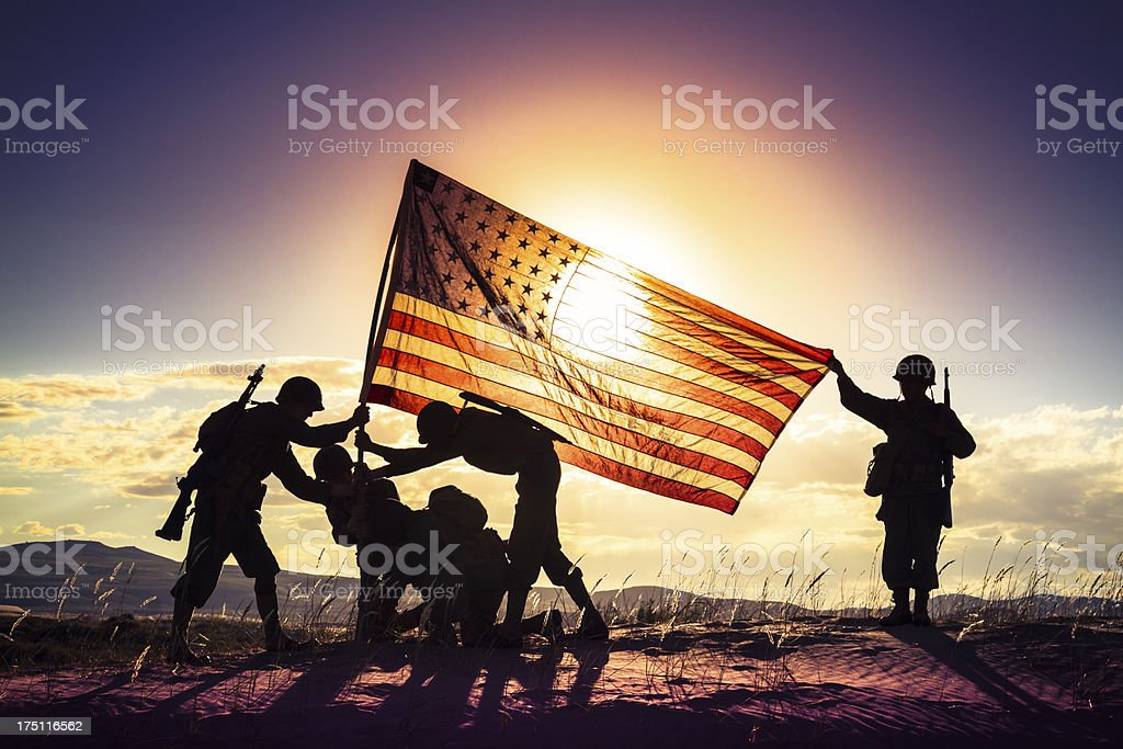 WWII Soldiers Raising The American Flag At Sunset stock photo