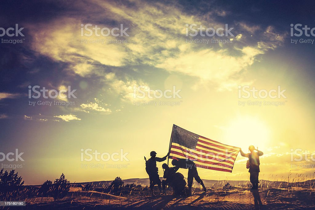 A Segunda Guerra Mundial soldados levantar a bandeira americana ao pôr-do-sol - foto de acervo
