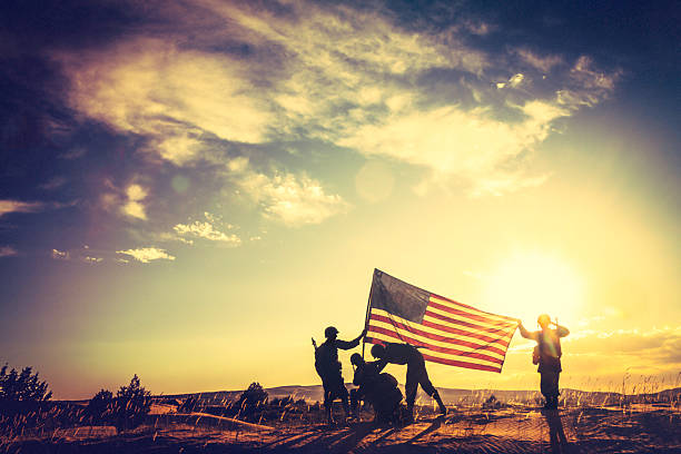wwii soldiers raising the american flag at sunset - armed forces stock photos and pictures