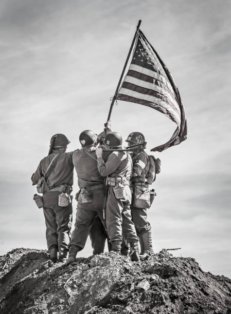 Soldiers Raising the US Flag Soldiers Raising the US Flag in celebration on top of a hill (Stock Image) desaturated stock pictures, royalty-free photos & images