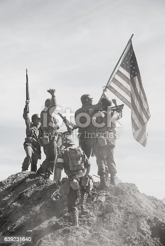Soldiers Raising the US Flag in celebration on top of a hill (Stock Image)