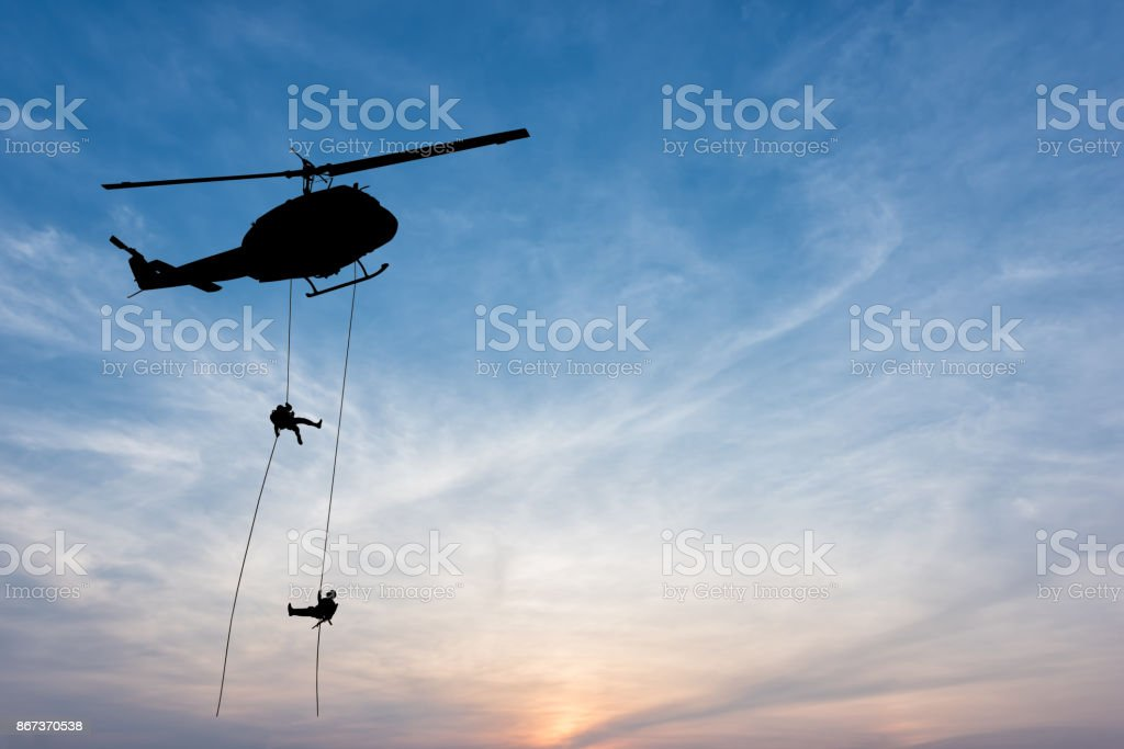 soldiers rescue helicopter operations on sunset sky background. stock photo