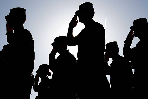 Soldiers Salute the Flag at Sunset stock photo