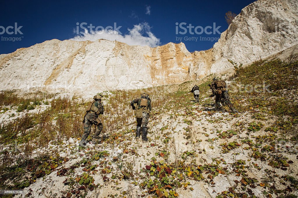 Soldiers team up the hill with a guide stock photo