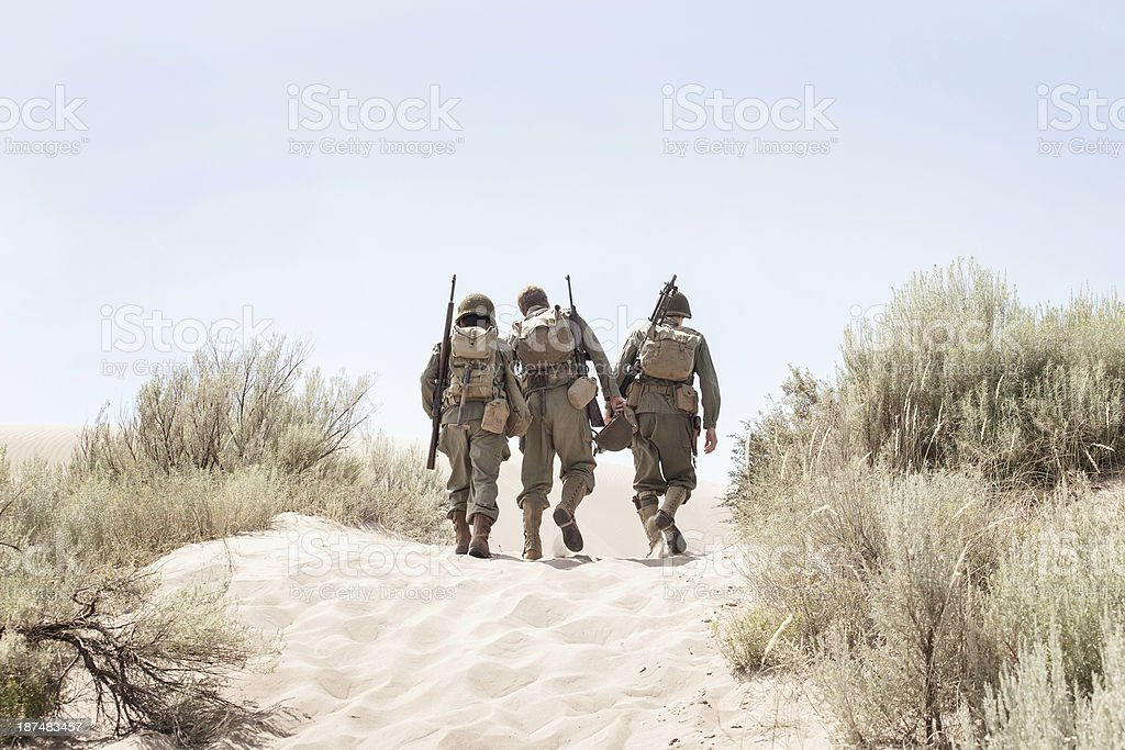 WWII soldiers trudging through white sand stock photo