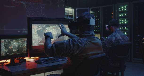 Soldiers using VR headset Medium shot of soldiers using VR headsets while sitting at their desks military base stock pictures, royalty-free photos & images