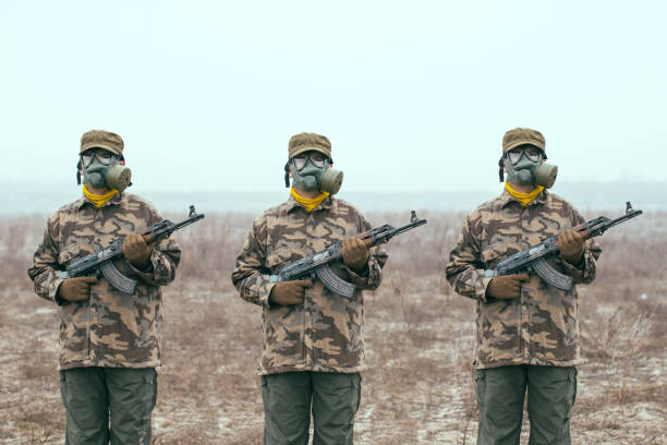 Soldiers with gas mask and automatic guns standing ready stock photo