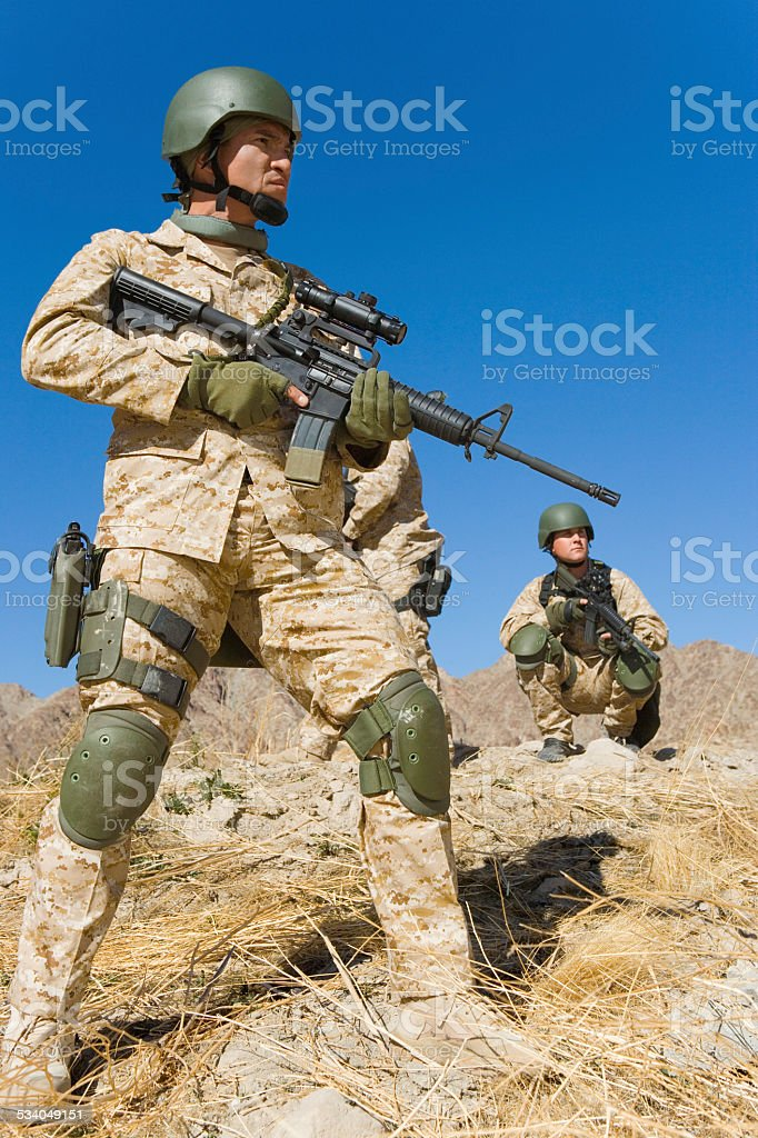 Soldiers With Rifles Patrolling Against Blue Sky royalty-free stock photo