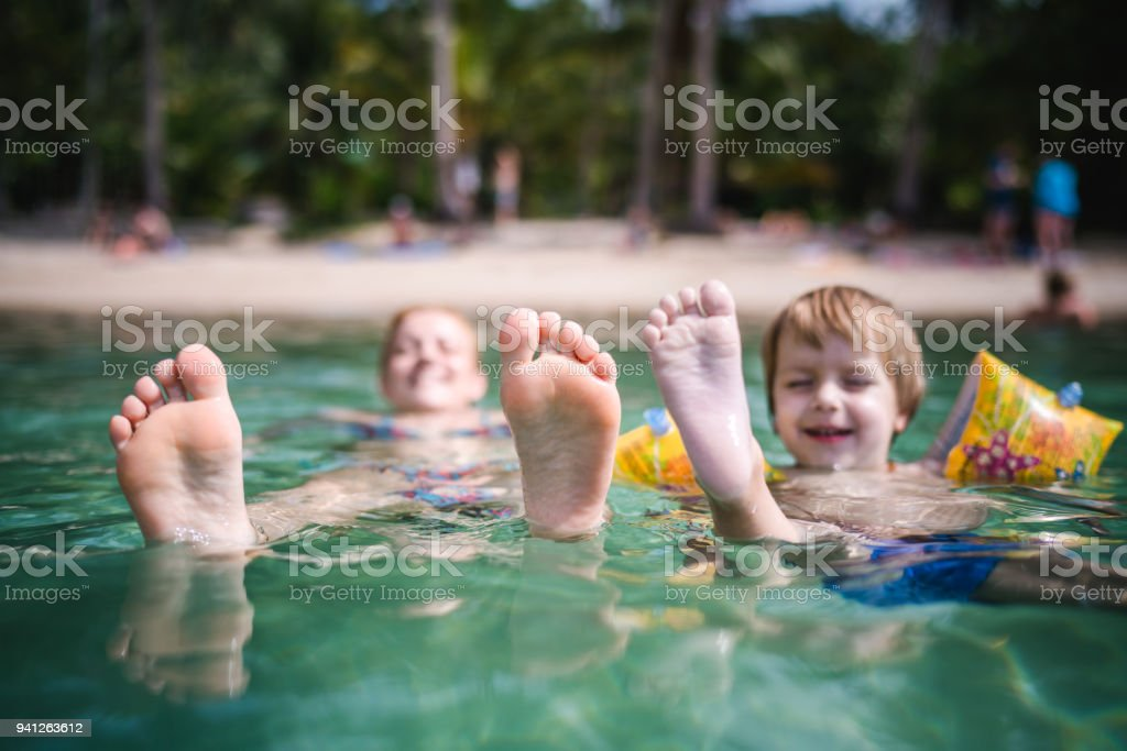 Sole of feet of little boy and his mother in the sea. stock photo