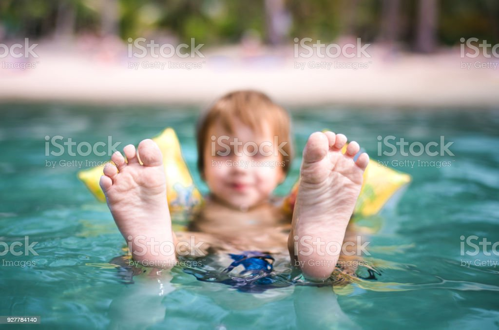 Sole of feet of little boy enjoying in the sea. stock photo
