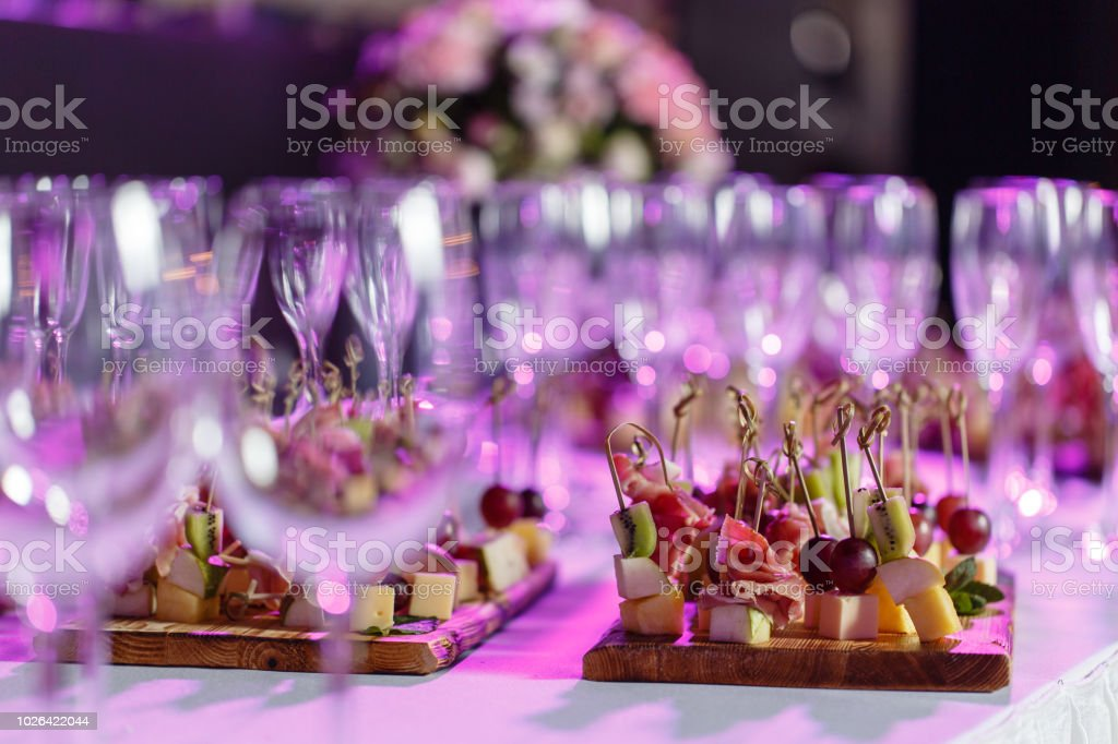 Solemn Happy New Year Banquet Lot Of Glasses Champagne Or Wine On The Table In Restaurant Buffet Table With Lots Of Delicious Snacks Canapes Bruschetta And Little Desserts On Wooden Plate Board