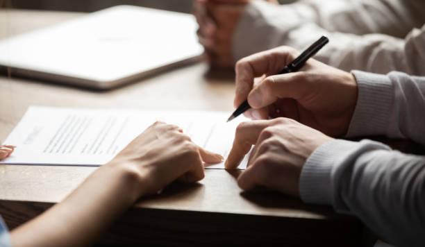 abogado que señala el contrato que muestra al cliente dónde escribir la firma - abogado fotografías e imágenes de stock