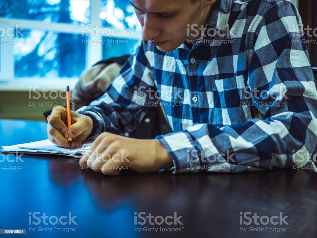 solid businessman in checkered shirt taking notes on paper sitting at the table - Royalty-free Adult Stock Photo
