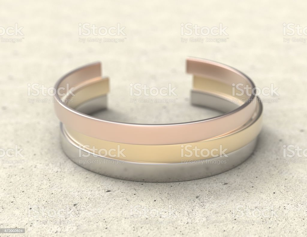 Solid metal bracelet in three colors on a stone table. Mockup close-up stock photo