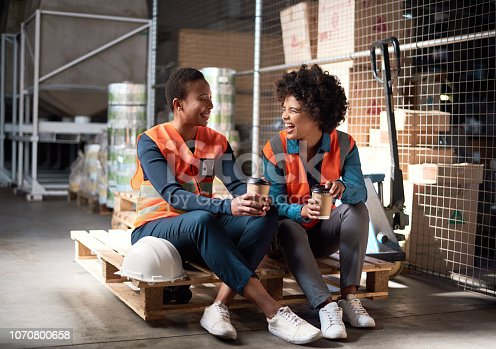 Shot of two young women having a coffee break together in a factory