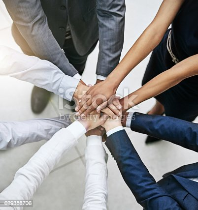 Cropped shot of a team of colleagues joining their hands together in unity