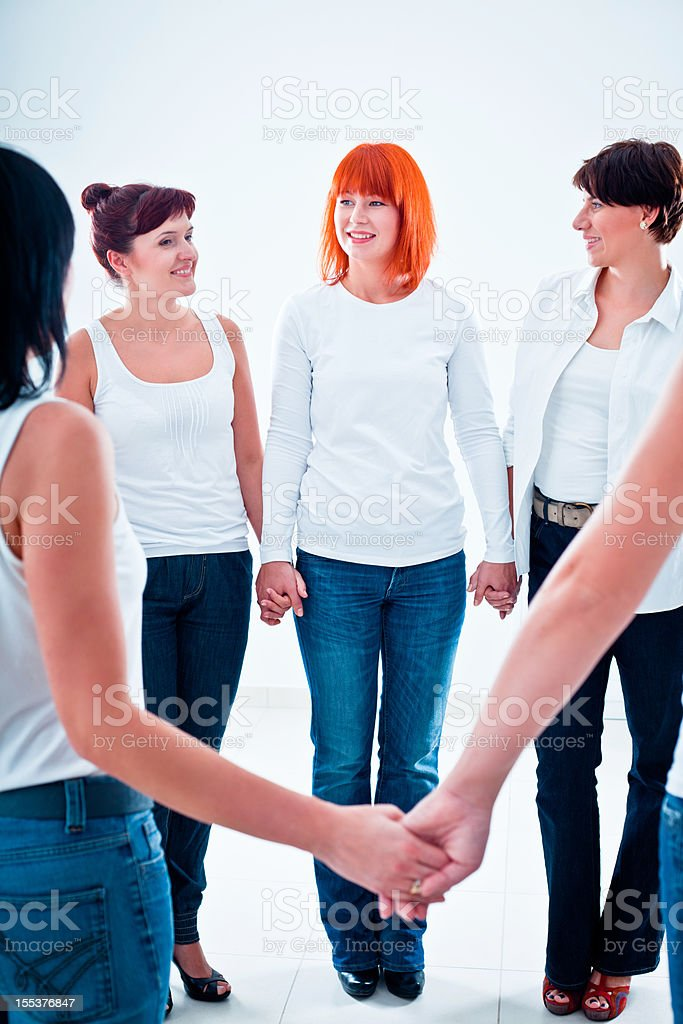 Solidarity Teamwork concept. Group of smiling women standing in the cicrle and holding hands.  Adult Stock Photo
