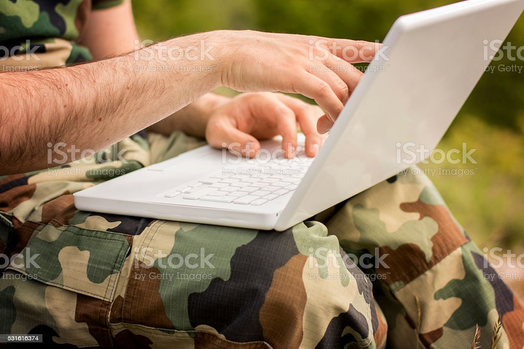 Solider on laptop, close-up stock photo
