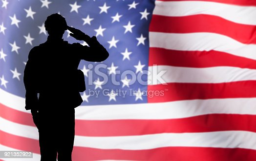 istock Solider Saluting Against The American Flag 921352922